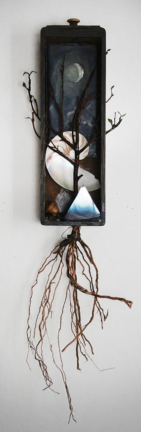 """Catherine Nash  Phases  Mixed media assemblage in an antique sewing machine drawer, wood carving, encaustic branch, roots, paper """"leaves"""", seeds, mirror, nautilus shell.  31""""h X 9""""w X 6""""d 2011"""