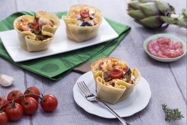 I cestini si pasta fresca con carciofi, gamberetti e pomodorini confit sono degli scrigni e farciti con sfiziosi ingredienti.