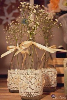 Outra forma bonita de expor as flores. O arranjo está muito simples, na minha opinião, mas a ideia de comprar rendas e aplicá-las nos vasinhos de flores é ótima, além de ornar com o seu vestido, caso seja feito nesse material.
