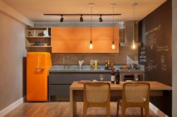 área da cozinha é mais alegre, com armários e geladeira na cor laranja + bancada e armário inferior na cor cinza. Ao lado, o closet e o banheiro.