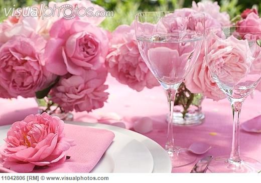 Romantic place setting with simple crockery, rose pink table linen and posies of roses
