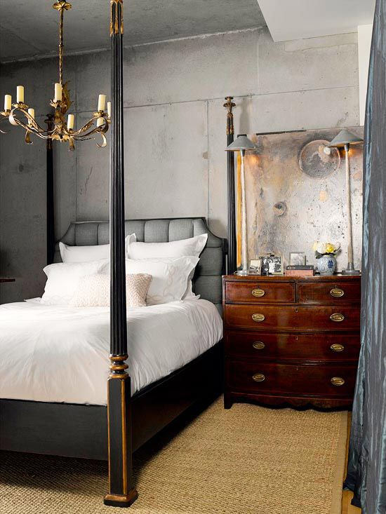 Opposites Attract: Taking its color cues from industrial concrete walls, this bedroom features a tufted headboard covered in steely gray linen and a contemporary painting rendered in metallic silvers. An antique four-poster and walnut chest continue the traditional theme, warming up the potential coolness of the concrete walls with a touch of timeless formality.