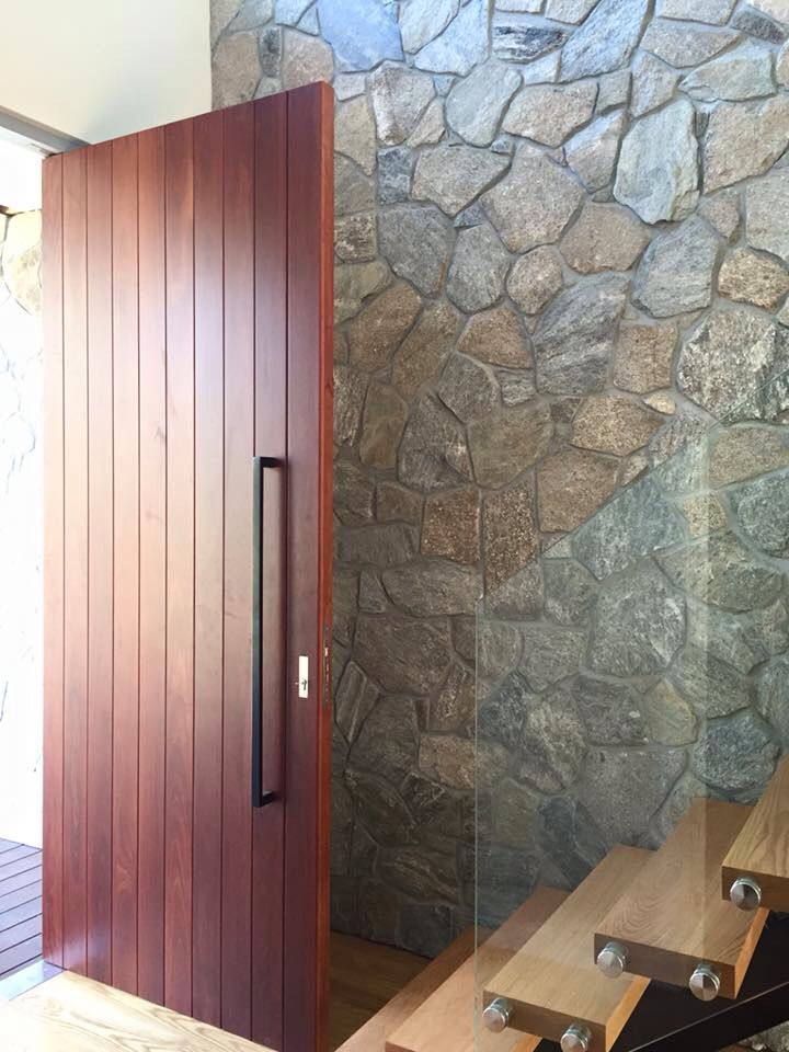 Stone wall and oversize custom built entry door in Sorrento home built by Jigsaw Projects. www.jigsawprojects.com.au