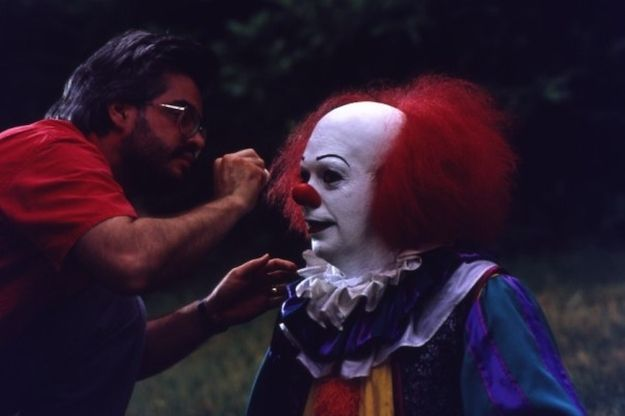 """40 Awesome Behind The Scenes Photos From Horror Movies--Pennywise in """"It"""" getting a make up touch up"""
