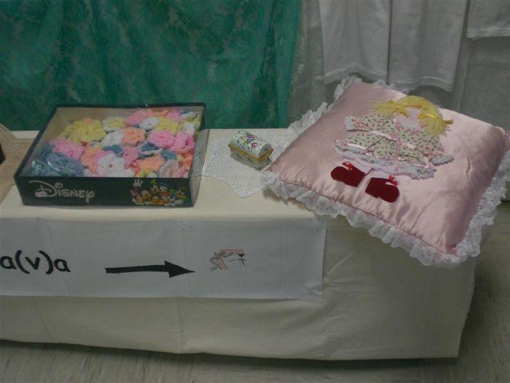 Giochi di lana per copertine, e cuscino con bambolina in rilievo.