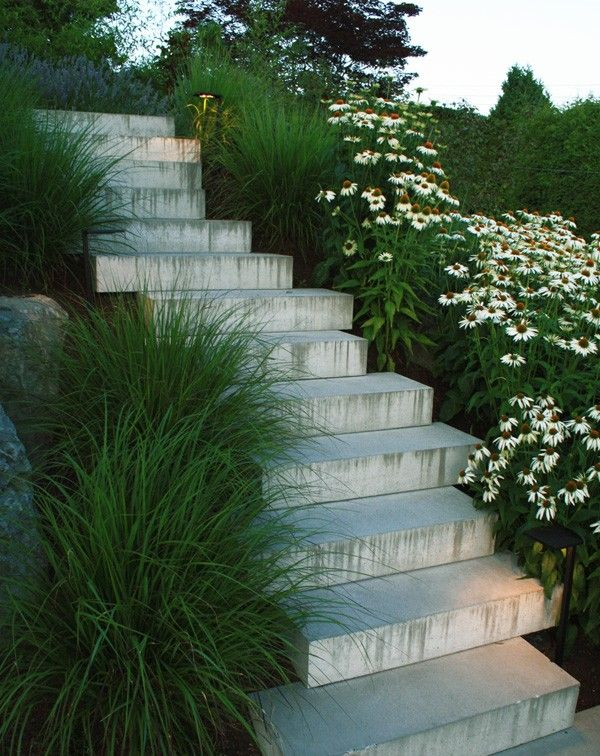 Pathway Lights. If your stairs are flanked by greenery, consider pathway lights, fitted with canopies to direct light downward. Garden lights tucked in grasses of staggered stairs by Botanica Design in Vancouver, BC.