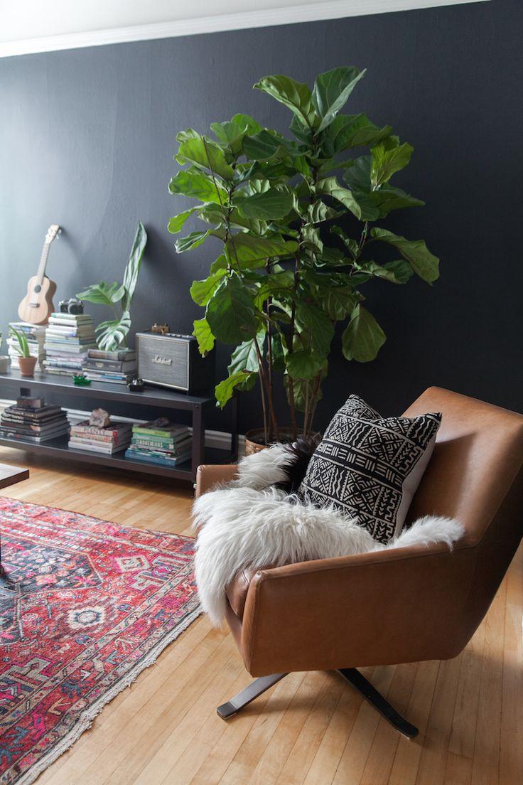 De blauwe muur combineert goed met de bruine leren stoel en de groene plant