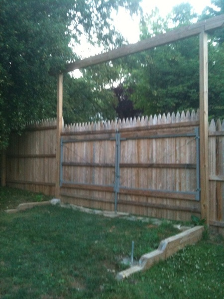 A double gate installed with a 6' stockade fence  stabilized with a horse ranch style arbor.