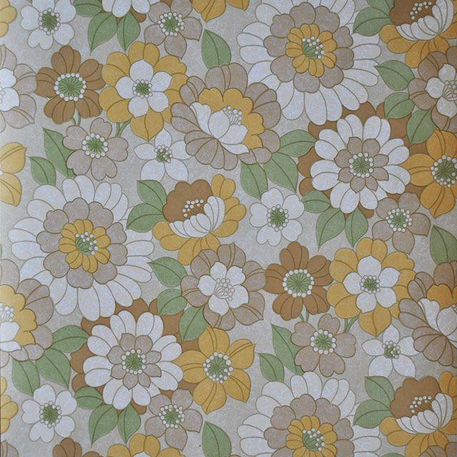 Bloem behang in okergeel, bruin en beige met groen, op een beige ondergrond. Diverse patroontjes in de kleurvlakken zorgen voor de kleurmelanges.