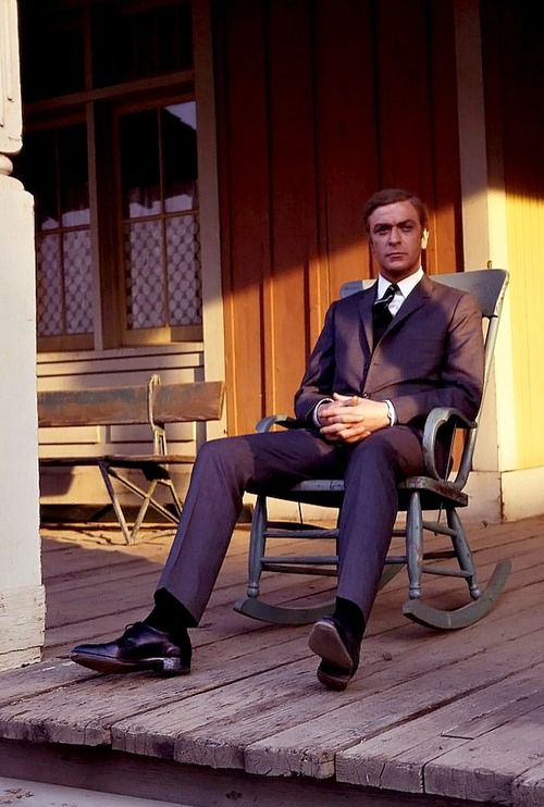 Michael Caine poses for a photo on a rocking chair on a mock up western street during a visit to the back lot at Universal Studios during time off from filming Gambit in Los Angeles on January 26, 1966
