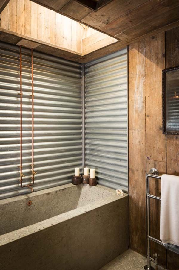 The bathroom features corrugated tin walls and a custom-built concrete bath and countertop. The space is illuminated by a skylight and is closed off for privacy by a sliding steel barn door.
