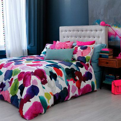 Love colour? Don't be afraid to use it in your bedroom - deep, blue and grey walls are the perfect calming background to this colourful duvet. Add an extra punch with a brightly painted bedside lamp.