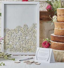 Gästebuch Holzherzen Die Hochzeitsgäste beschriften moderne Holzherzchen mit ihren individuellen Glückwünschen und werfen sie in den weißen Rahmen mit Glasfront.