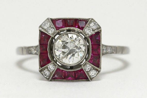 Art Deco era old mine diamond bezel set, accented by a halo of rubies. Seen at our shop in downtown Santa Barbara, California, or here on the web.