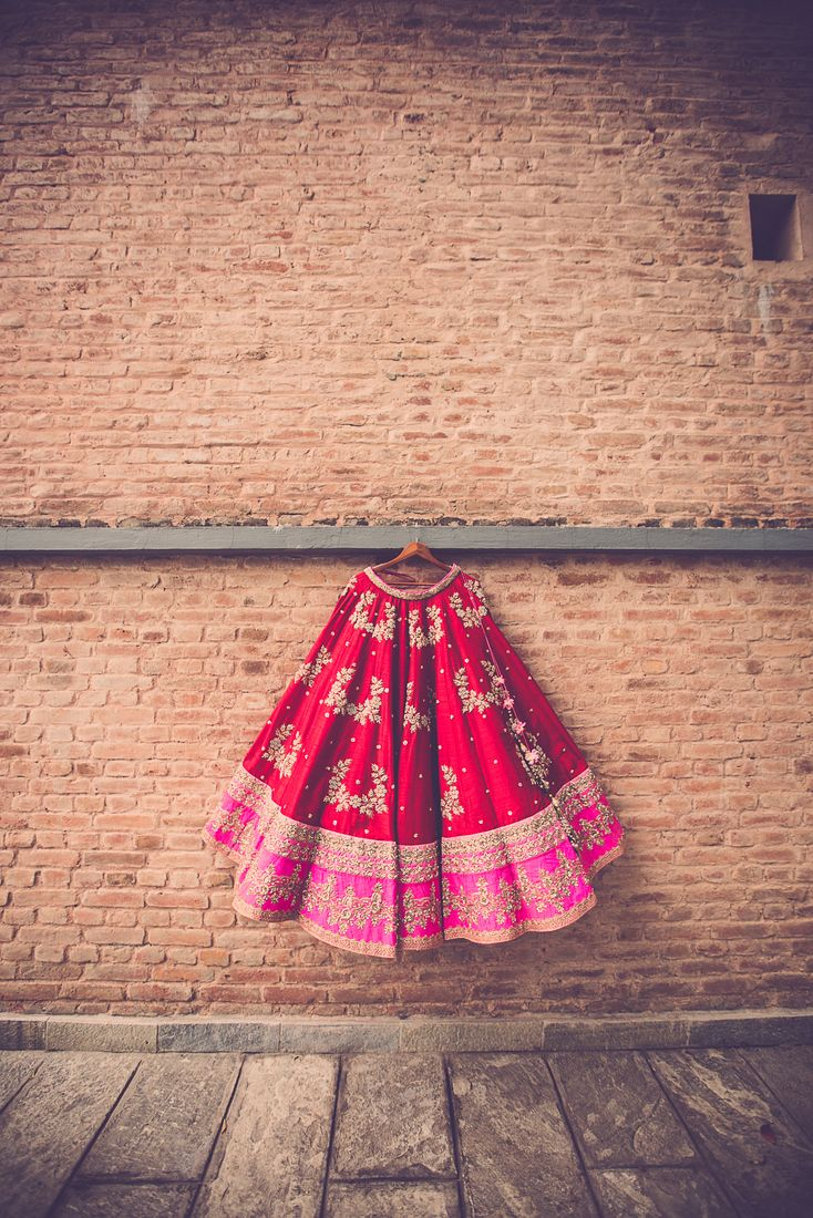 We are used to seeing brides wear floral printed Anushree Reddy outfits to their Sangeet & Mehendi, but a bride wearing one in a classic red to her wedding is rare. What's even rarer- choosing Nepal for your wedding destination. From quirky origami decor with neon tents at the mehendi to a