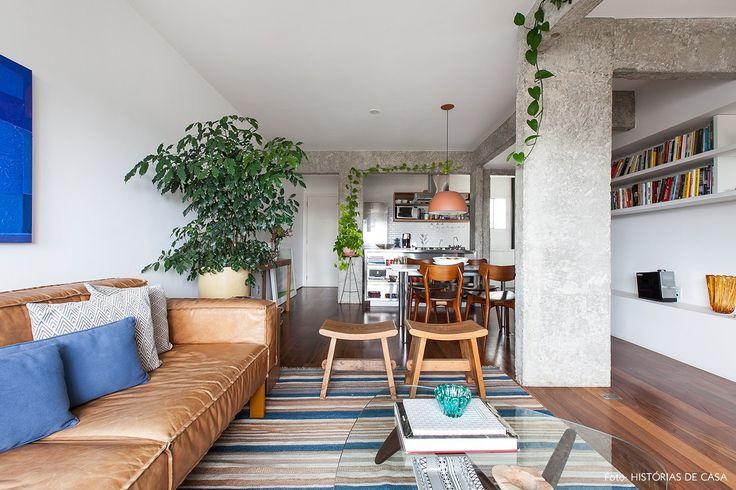 Sala de estar tem tapete listrado, sofá de couro caramelo e almofadas azuis.