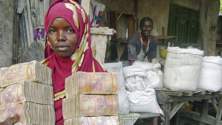 A moneychanger carrying Somali currency pose at the Bakara open air market in Mogadishu, October 10, 2008. The global financial crisis could hamper efforts to alleviate hunger in Africa, the U.N. Economic Commission for Africa said on Friday.