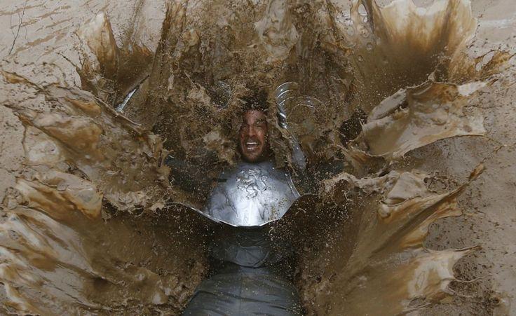 """Uomo duro nel fango. Un partecipante alla Gara annuale di beneficienza """"Tough Guy"""" cade nel fango, a Parton, nell'Inghilterra centrale (Reuters/Darren Staples)"""