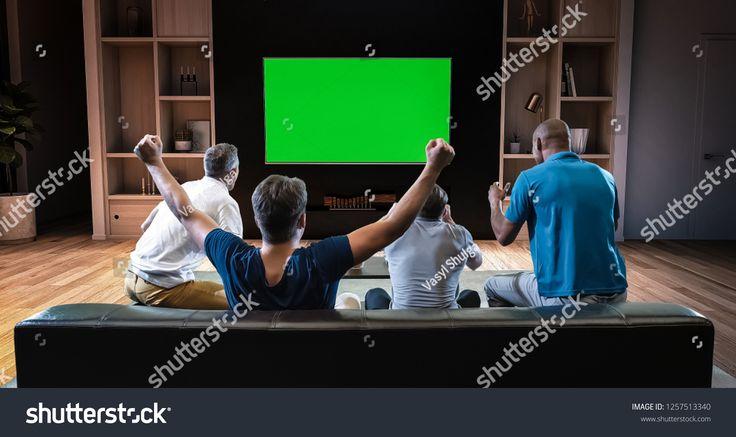 Un groupe d'étudiants est en train de regarder la télévision et de célébrer un joyeux moment sportif, …