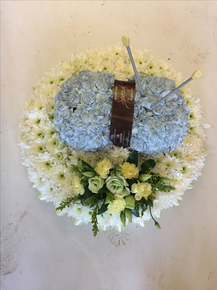 Knitting needles and a ball of wool as funeral flowers beautiful tribute
