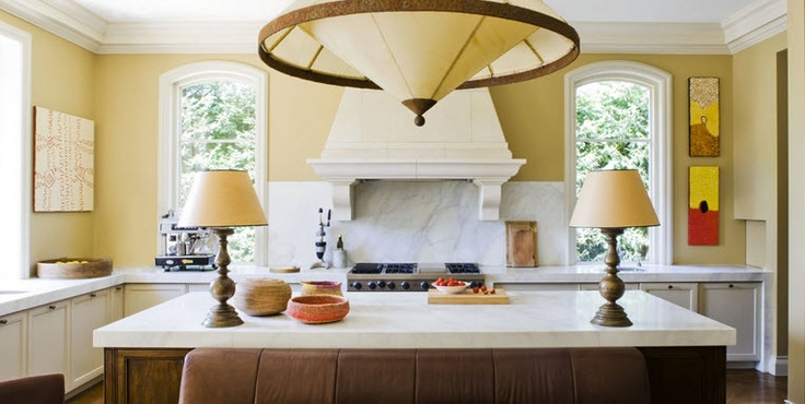 Classic cream units, pale worktop, over mantel above range with marble splash back. Contrasting wooden island again with a pale worktop.