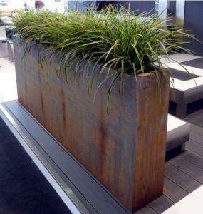 Pflanzgefäß aus Cortenstahl auf dem Deck Das Pflanzgefäß aus Cortenstahl im Freien bietet Privatsphäre und Kunst für angelegte Gärten