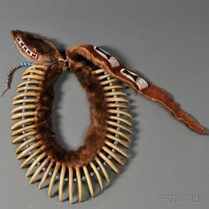 Pawnee-style Bear Claw Necklace, assembled by Milford Chandler (1889-1981)   Constructed with an otter skin painted red beadson the hide side, the head with a black and white beaded strip on red trade cloth, with forty large 19th century grizzly bear claws and large Italian bead spacers; includes a late otter hide drop with six beaded bear paws and two tie-on beaded strips (added by Joseph J. Rivera)   57,000$ ~ Sold