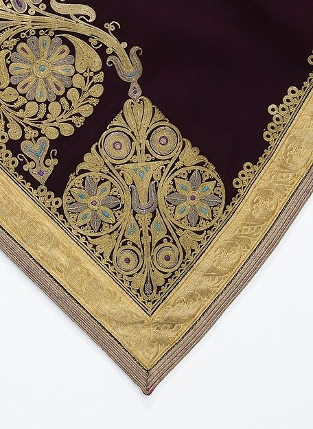 The careful placement and execution of motifs on this sleeveless coat are an example of fine workmanship. The use of solid color insets within the gold couched forms adds a gem-like quality to an extravagant surface