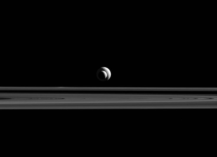 Two of Saturn's many moons line up for a special Cassini spacecraft photo op as they strike a pose with rings against a backdrop of the blackness of space.