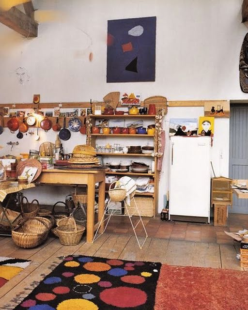 Alexander Calder's home. Living room detail: display of pots and pans, baskets. Calder rug on floor, painting on wall. Images from the book Calder at home.