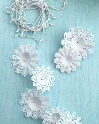 "Snowflake Lights  Create an idealized winter wonderland indoors using snowflake-like bouquet holders and a string of holiday lights.  To make one of these garlands, slide a store-bought paper bouquet holder over each bulb. Hang the ""snowflakes"" inside a doorway or a window, and then plug in the lights."
