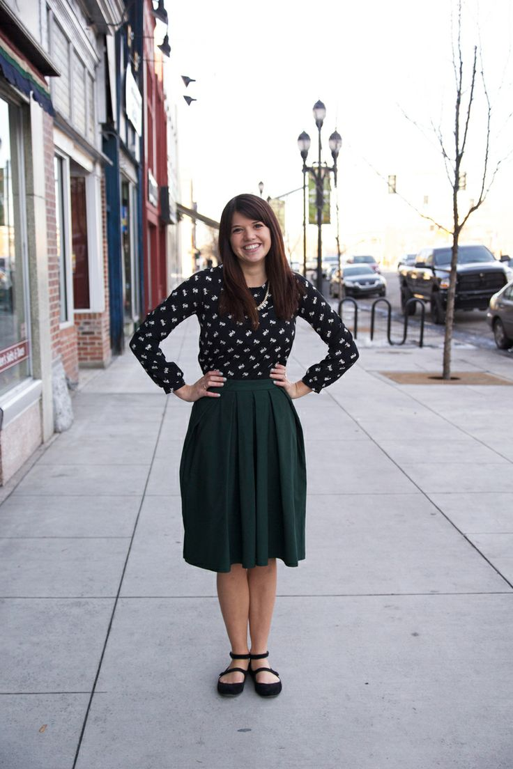 black and white patterned shirt, emerald green skirt, and black flats