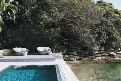 Swimming pool goals: inspiration for at-home summer relaxation: Dedon 'Orbit' woven rattan outdoor sofas from Domo provide luxurious poolside lounging where this deck meets Sydney harbor, at a home by Thomas Hamel.