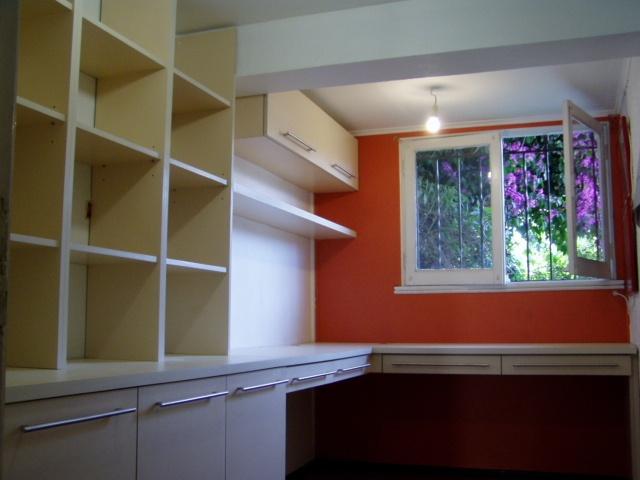 Biblioteca y escritorios en melamina engrosada color vainilla.  Muebles aéreos.  Tiradores metálicos satinados.  Rieles telescópicos.
