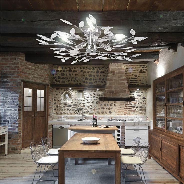 una cucina rustica illuminata da un lampadario ispirato alla natura con lampade led a candela a luce bianca