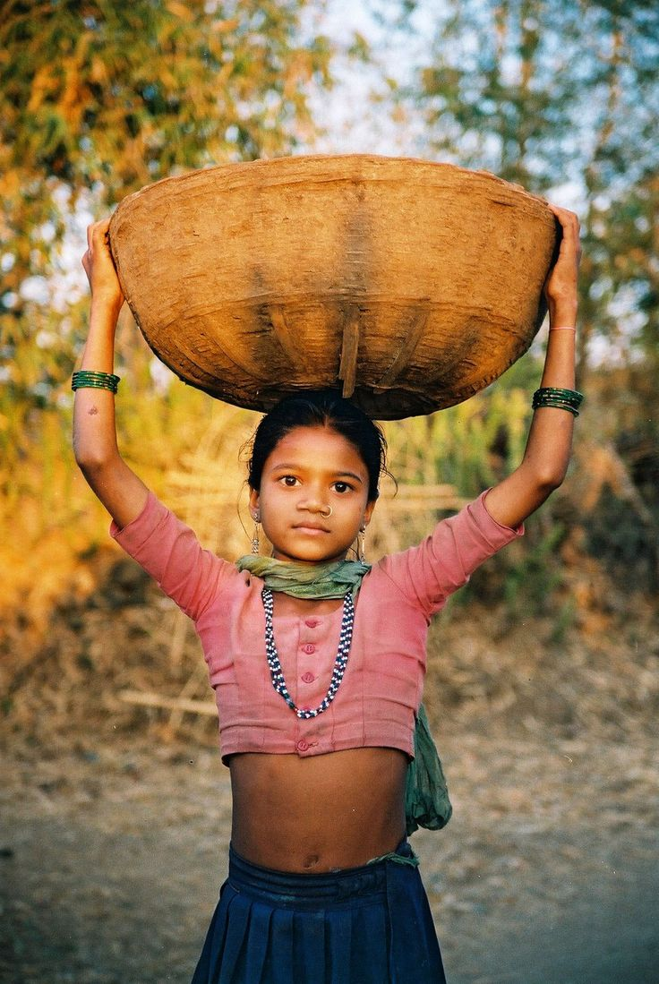 Beautiful Little Girl Carries A Big Load On Her Head With Dignity