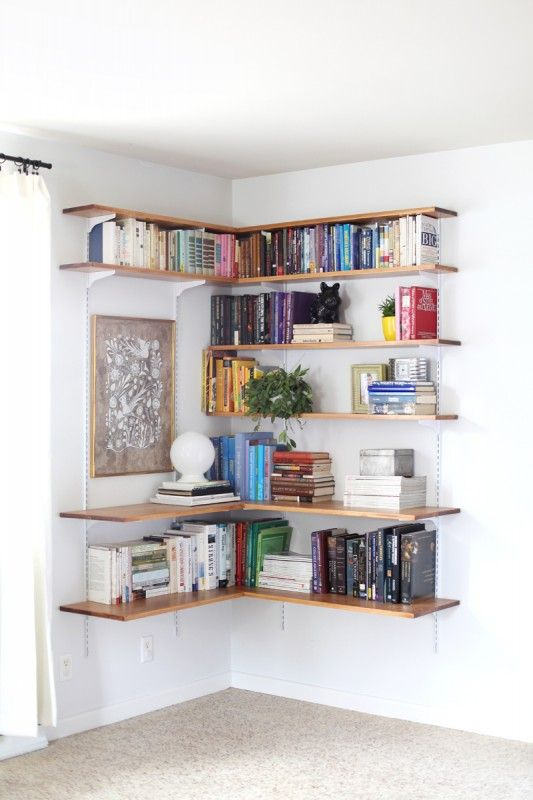 Great use of inexpensive track shelving! Use the brackets and tracks but swap in wood shelves for an industrial look, and this corner shelf looks amazing!