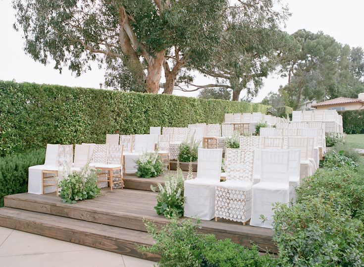 The couple's wedding guests sat atop wooden ceremony chairs covered with white lace slipcovers that were placed on wooden risers. Arrangements of greenery and ivory wildflowers lined the aisle. #weddingceremony #decor Photography: Elizabeth Messina. Read More: http://www.insideweddings.com/weddings/ethereal-garden-inspired-morning-ceremony-alfresco-brunch/582/