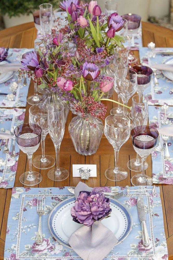 Sobre o centro da mesa, peônias, micro- orquídeas, ninféias, orquídeas zygopetalum, tulipas em tons de uva e roxo, e limonium, foram dispostos de forma leve e descontraída, pela querida Dani Mendes da Milplantas, em quatro vasos Muranos iguais.
