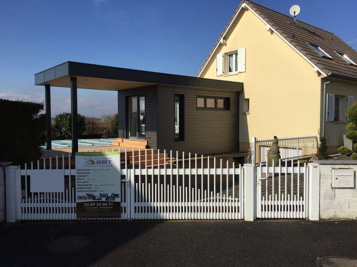 Abri de jardin en bois avec terrasse couverte pour une cuisine d'été et avec porte d'accès bardé et dissimulé dans le bardage. Par ABT Construction Bois.