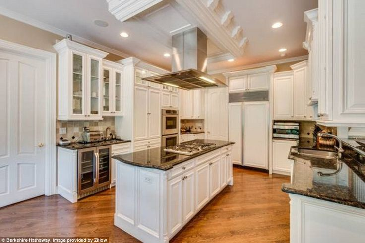 Another hallway on the left of the home's entry takes you to an eat-in kitchen that has an island in the center, stainless steel appliances, and a mini wine refrigerator