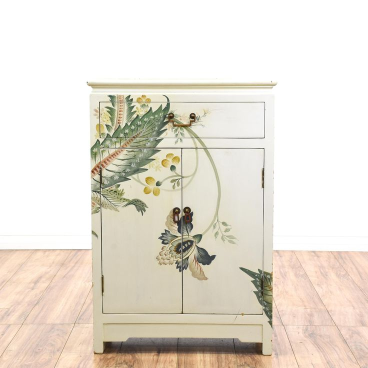 This gorgeous cabinet is featured in a solid wood with a white paint finish. This Asian style end table has gold bamboo motifs, beautiful flowers adorning the frontside, 2 panel doors, and a flat drawer. A stunning nightstand that's sure to garner compliments! #asian #storage #cabinet #sandiegovintage #vintagefurniture