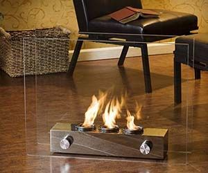 Mini Glass Fireplace. Now you can scrap that old tatty looking portable heater and upgrade to one of these very modern looking mini glass fireplaces! Awesome!