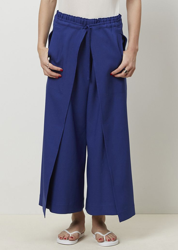 Wide leg full pant in polyester. Elastic waistband. Wrap around and tie split front detail with pockets. Hand was in cold water or dry clean. Do not bleach. Do not tumble dry.