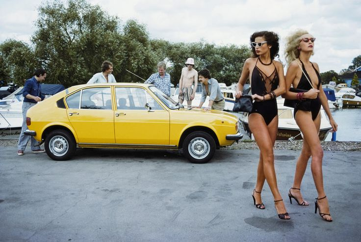 Two young women on a fashion shoot fail to catch the eyes of a group of men admiring an Alfa Romeo car, August 1979. Photograph: Brian Duffy/Getty Images