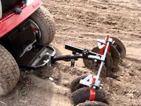 Garden tractor planting potato's with disk harrow