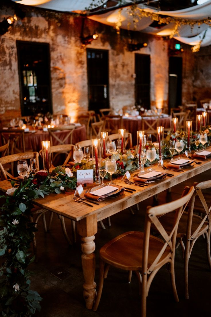 wedding family style seating // Mt Washington Mill Dye House // Baltimore MD // farm tables // garland // greenery // intimate reception dinner // candle lit // burgundy candle sticks // moody // rustic chic // exposed brick // fall wedding inspiration // palette inspiration
