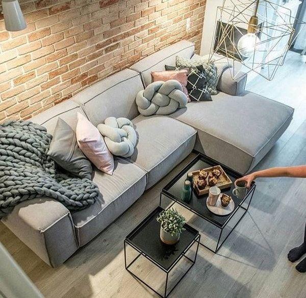 Salas pequeñas. Pared de ladrillo a la vista en salones. Cojines modernos. Sofá esquinero gris.