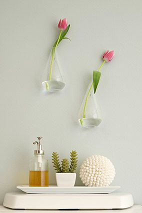 """One quick way we love to update a bathroom is to hang something waterproof on the wall so you don't have to worry about an expensive art print getting ruined by the steam. You could add a shelf with glass canisters of cotton balls and cotton swabs or hang floating glass vases from the wall. You can also add style to the top of your toilet tank with a ceramic tray full of pretty things like soaps, a piece of faux coral or a shell ball."""
