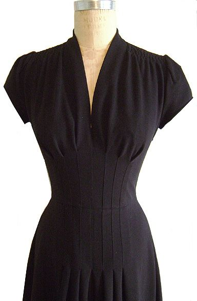 great use of darts. This style features a v neckline and classic darted short sleeves. The darts extend from under the bust to the fullness of the hips . There is gathering at the top of the shoulder and the skirt has a kicky wide a-line shape. The back is simple and fitted with only a waist seam. This is a thick knit with the look of a vintage wool jersey without the scratch!